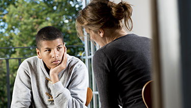 Woman speaking with adolescent.