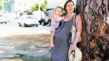 Pregnant woman holding a child with bags.