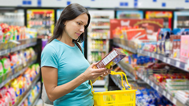 Woman checking food labels at a supermarket.