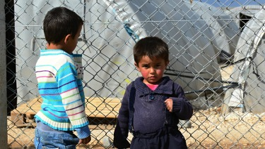 Two refugee children standing by a fence.